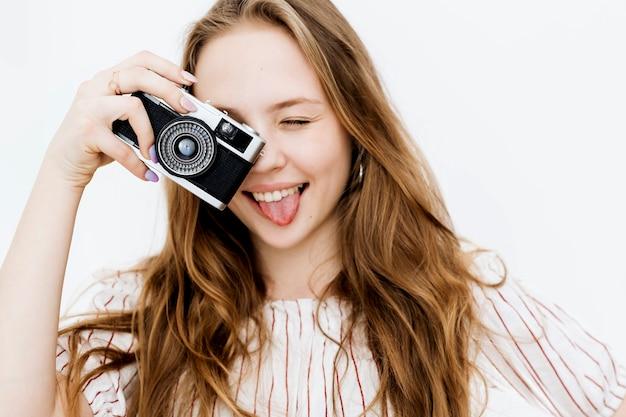 Donna allegra che scatta una foto con una cinepresa