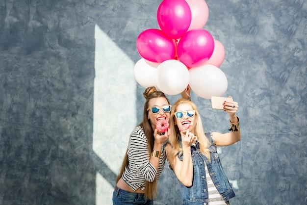 Donne allegre che si divertono con ciambelle dolci e palloncini sullo sfondo della parete blu