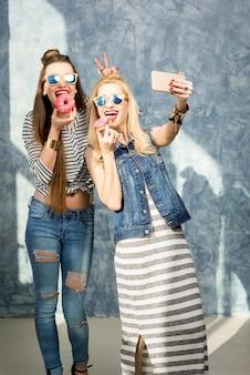 Donne giocose che si divertono con ciambelle dolci sullo sfondo blu della parete