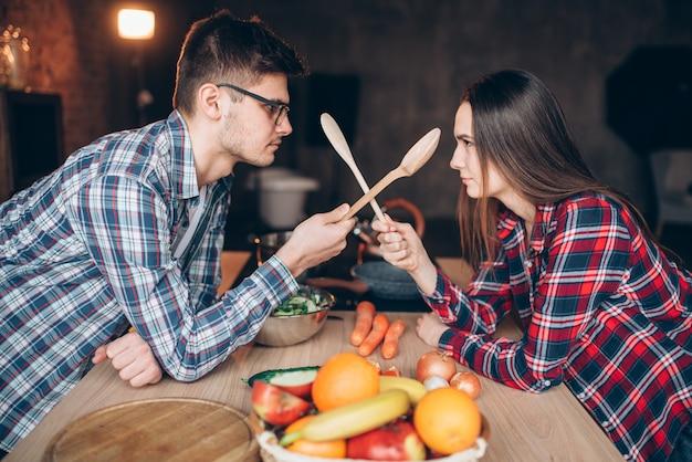Giocoso giovane coppia lotta con cucchiai di legno in cucina durante la cottura della colazione. uomo e donna che preparano insalata di verdure, famiglia felice insieme