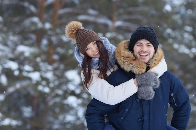Giovani coppie allegre che camminano nella foresta di inverno nevoso. sfocatura sfondo, copyspace