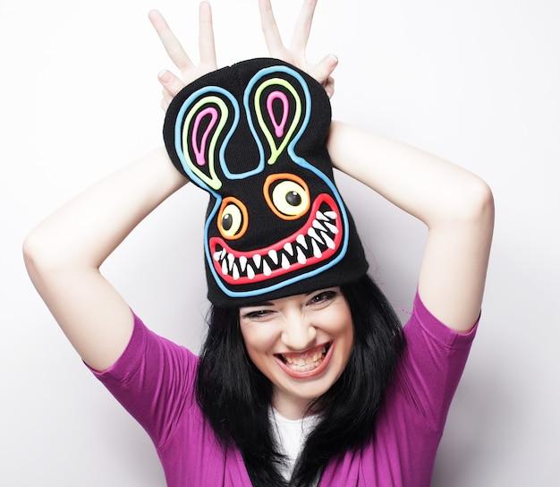 Giocosa giovane donna in buffo cappello con coniglio, girato in studio