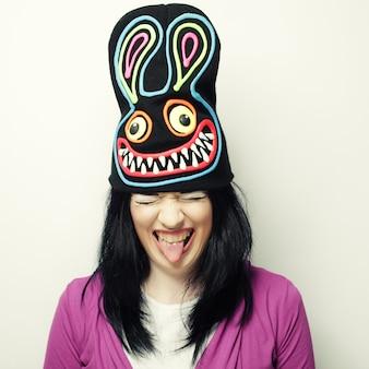 Giocosa giovane donna in buffo cappello con coniglio