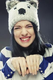 Giovane donna allegra in cappello invernale divertente