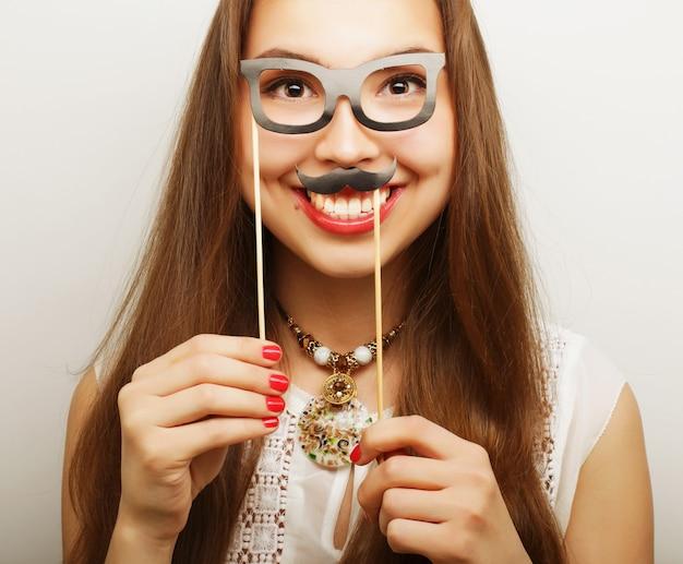 Giocosa giovane donna con baffi e occhiali su un bastone. pronto per la festa.