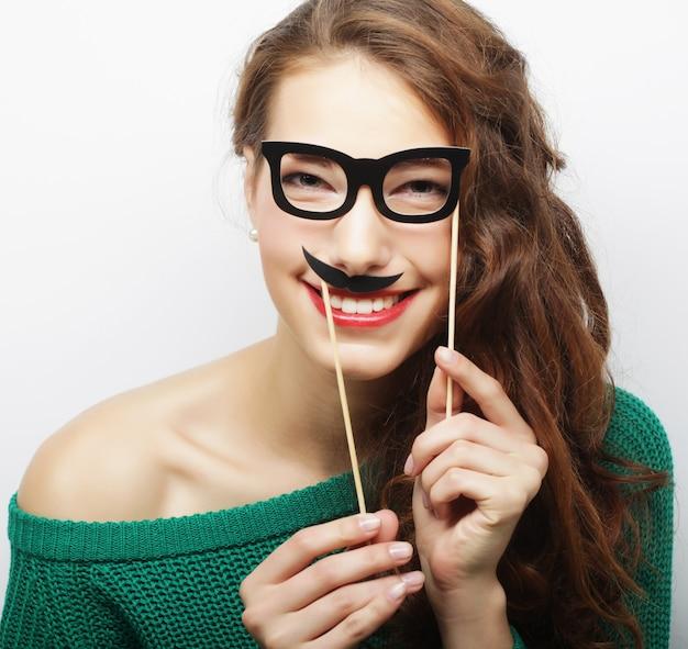Giocosa giovane donna con occhiali da festa e baffi finti