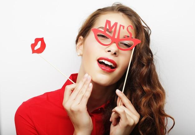 Giovane donna giocosa che tiene gli occhiali da festa
