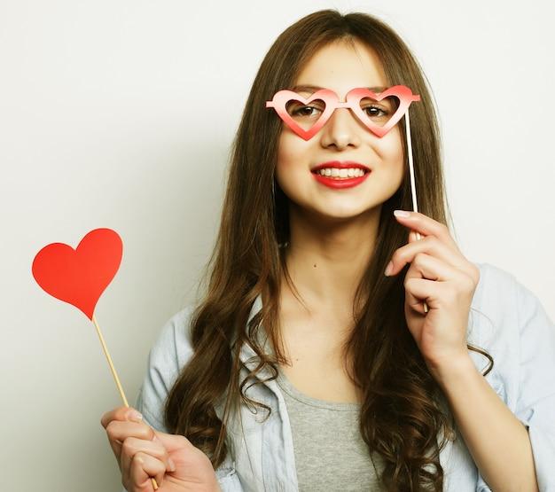Giovane donna allegra che tiene gli occhiali da festa