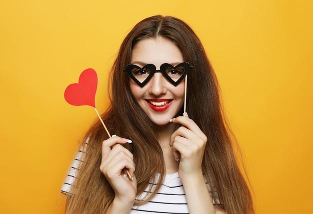 Giocosa giovane donna pronta per la festa su giallo Foto Premium