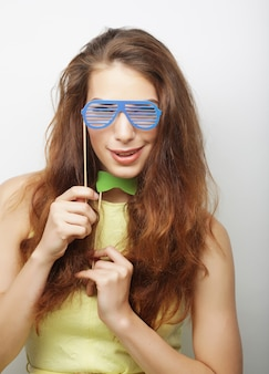 Giocosa giovane donna con occhiali finti, pronta per la festa