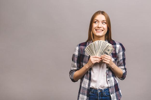 Giovane donna allegra con capelli lunghi che tengono mazzo di banconote e distogliere lo sguardo dei soldi
