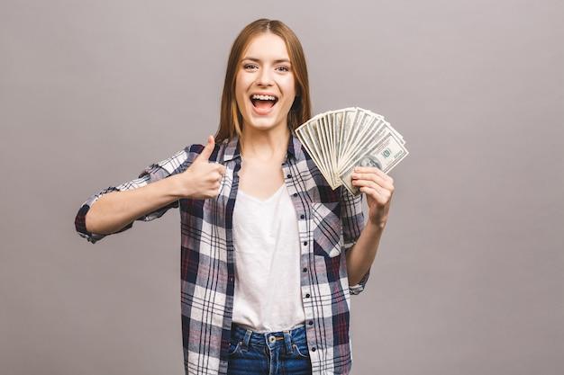 Giovane donna allegra con capelli lunghi che tengono mazzo di banconote dei soldi e che esaminano macchina fotografica. pollice su.
