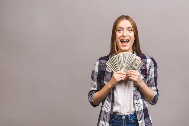 Giovane donna allegra con capelli lunghi che tengono mazzo di banconote dei soldi e che esaminano macchina fotografica