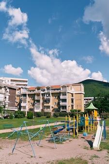 Parco giochi nel cortile di edifici di cinque piani sullo sfondo delle montagne