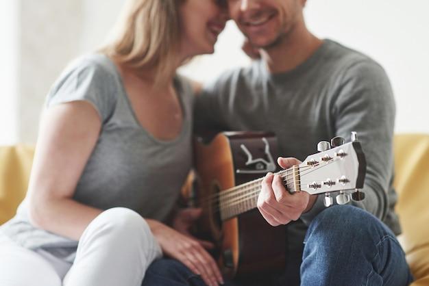 Suonare la chitarra acustica per la ragazza nel soggiorno della nuova casa.