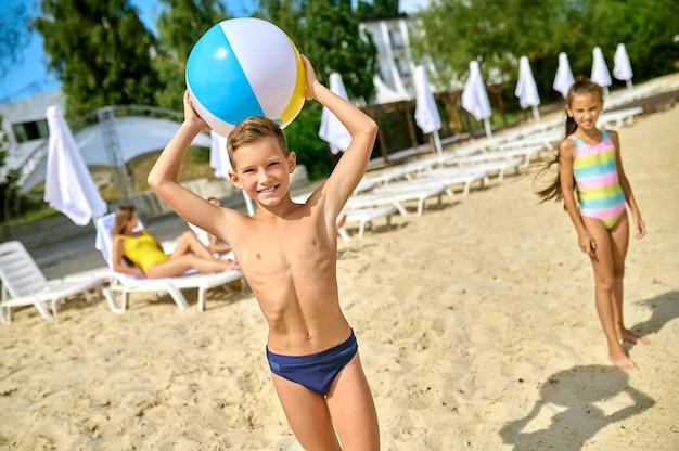 Giocare su una spiaggia. bambini che giocano a palla su una spiaggia