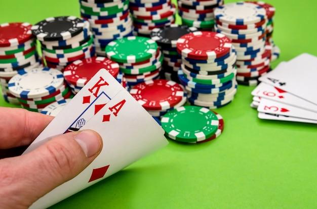 Combinazione di carte da gioco in mano d'uomo, su sfondo verde