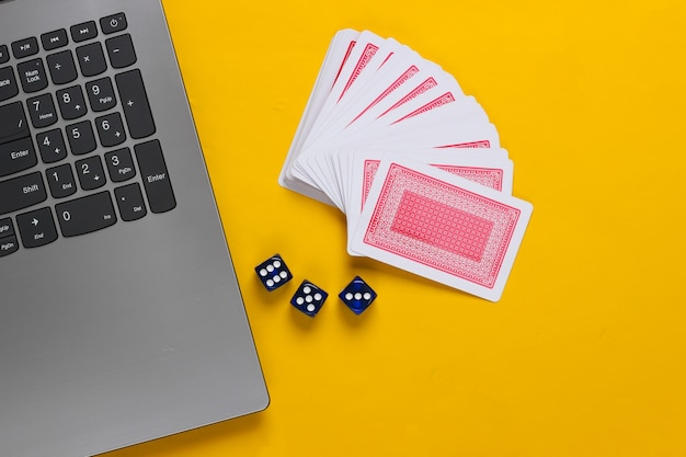 Carte da gioco e dadi blu, tastiera del computer portatile su sfondo giallo. casinò di poker online. vista dall'alto