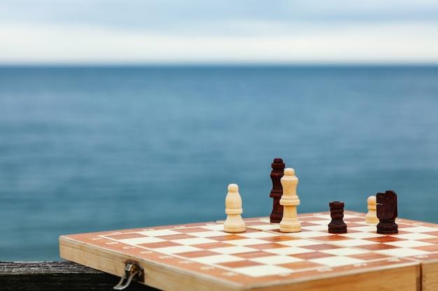 Giocare a scacchi su una tavola sulla spiaggia. scacchiera sul mare in una giornata di sole. vacanze sulla costa.