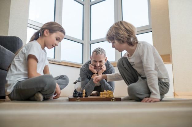 Giocare a scacchi. fratelli che giocano a scacchi mentre il padre guarda