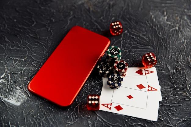 Carte da gioco chip dadi rossi e smartphone