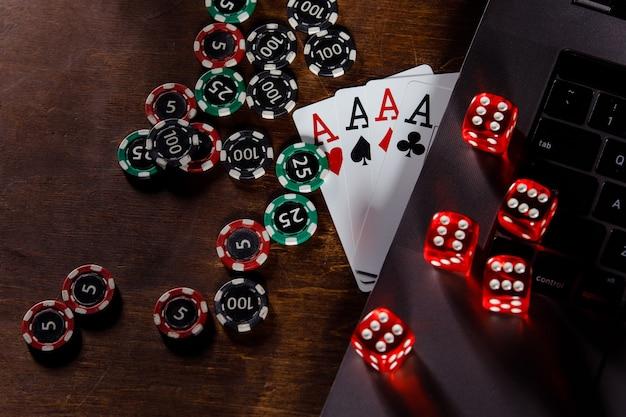Giocando a dadi rossi e carte con assi su uno sfondo di legno