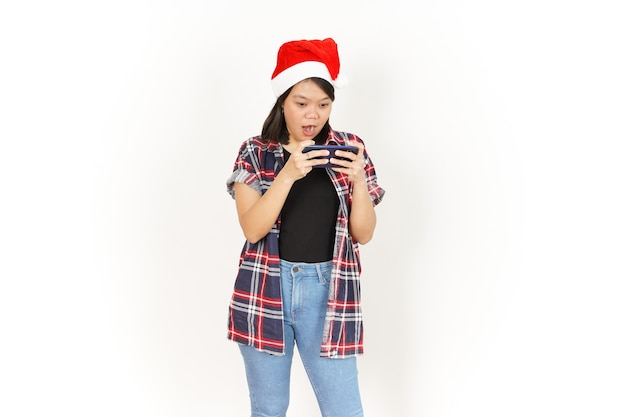 Gioco su smartphone di una bella donna asiatica che indossa una camicia a quadri rossa e un cappello da babbo natale