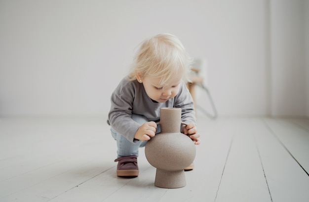 Giocare in casa con un vaso di fiori. interni luminosi ed eleganti dell'appartamento. la piccola figlia è una ragazza bionda caucasica in un elegante abito beige