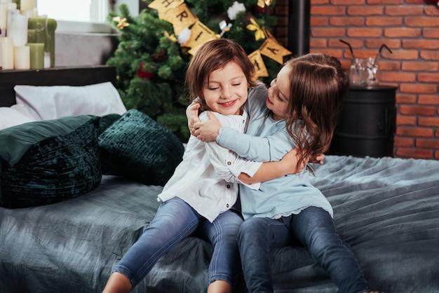 Giocare e abbracciarsi. i bambini si siede sul letto con sfondo decorativo. concezione del nuovo anno