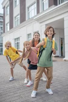 Giocando. scolari che giocano nel cortile della scuola e si sentono felici