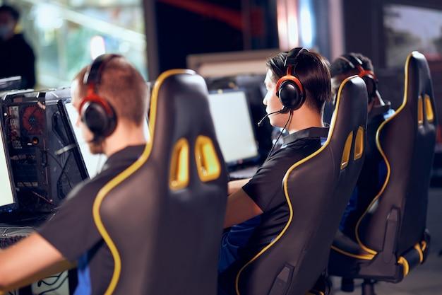 Giocare con i videogiochi. vista posteriore dei giocatori di cyber sport professionisti che indossano le cuffie che partecipano al torneo di esports