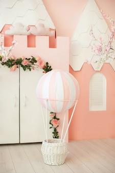 Sala giochi con tenda da castello rosa per bambini. camera dei bambini per una piccola principessa. decorazioni per una festa per bambini. una stanza con tenda, porta bianca e palloncino. kindergarten, sala giochi. interno