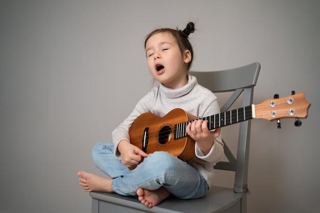 Suona l'ukulele e canta. sviluppo della prima infanzia. bella bambina praticando cantando e suonando la chitarra