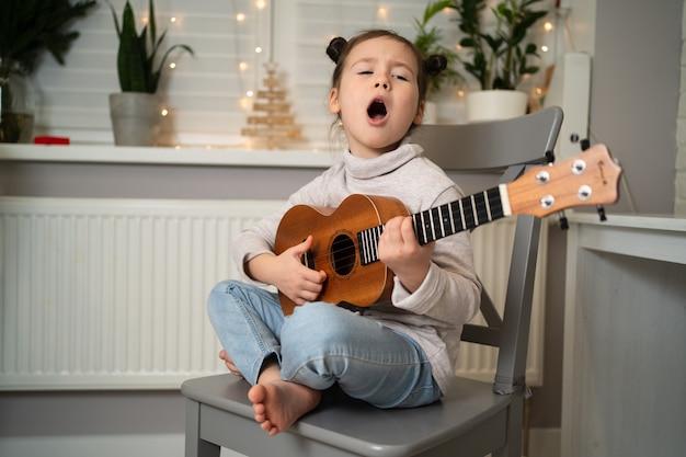 Suona l'ukulele e canta. sviluppo della prima infanzia. la ragazza ha talento musicale. bella bambina praticando cantando e suonando la chitarra.