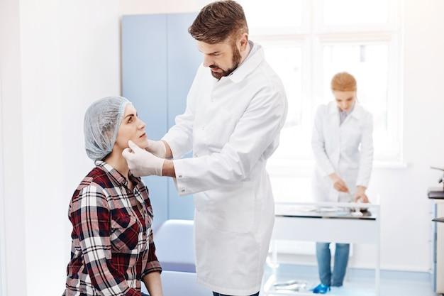 Piacevole donna attraente ansiosa che guarda il suo chirurgo plastico ed è preoccupata mentre si prepara a un intervento di chirurgia plastica