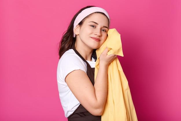 Piacevole carismatica femmina in piedi isolata sul muro rosa in studio, indossa grembiule marrone, maglietta bianca e fascia, premendo la camicia gialla sul suo corpo, godendo i risultati del lavaggio.