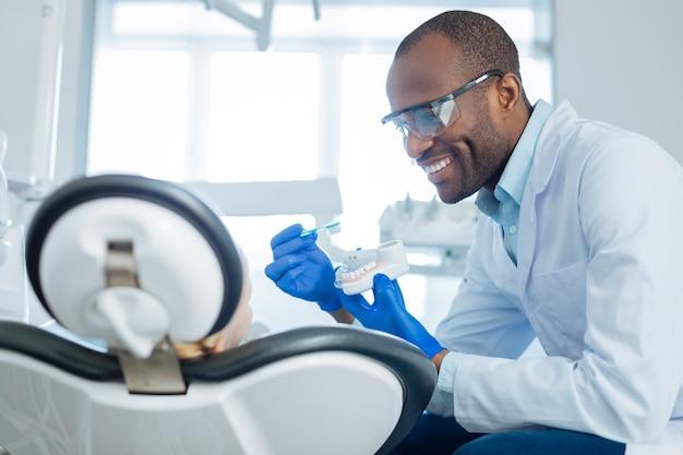 Piacevole uomo allegro che parla della corretta cura dei denti e mostra al suo piccolo paziente come lavarsi i denti correttamente