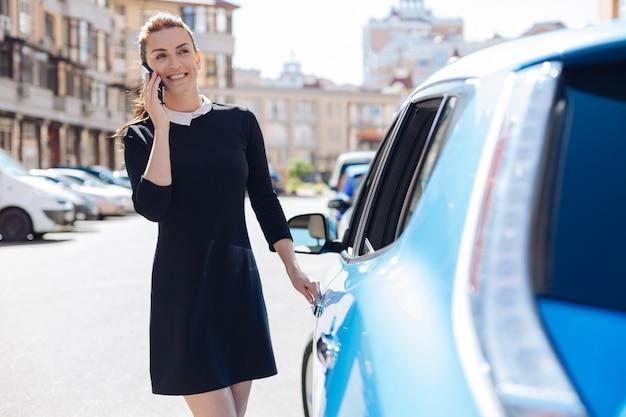 Comunicazione piacevole. allegro felice giovane imprenditrice tenendo il suo telefono cellulare e sorridente pur avendo una piacevole conversazione telefonica