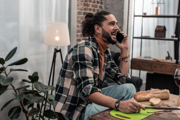 Comunicazione piacevole. felice uomo positivo che sorride mentre parla con il suo amico