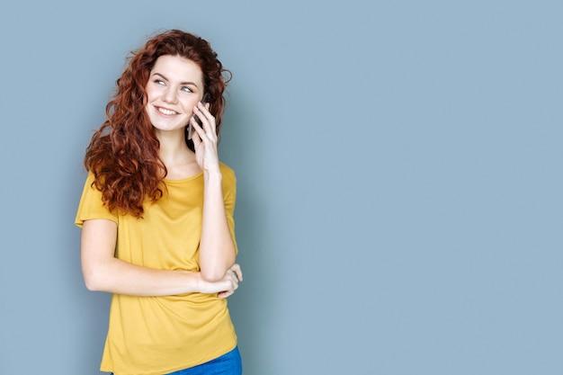 Comunicazione piacevole. gioiosa attraente giovane donna sorridente e avere una conversazione telefonica mentre in piedi su sfondo blu