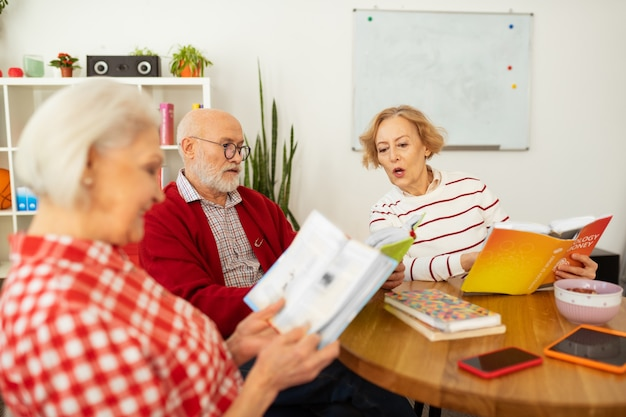 Comunicazione piacevole. bella donna anziana che parla con la sua amica mentre tiene un libro tra le mani