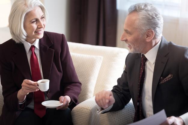 Piacevole conversazione. allegra imprenditrice invecchiata felice guardando il suo manager e seduto in hotel mentre discute del progetto con il suo collega e beve caffè