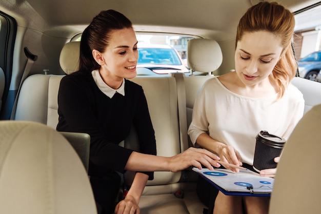 Piacevole collaborazione. donne di affari intelligenti e simpatiche deliziate sedute in macchina e che parlano tra loro mentre lavorano insieme