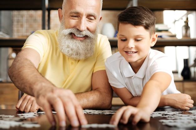 Giornata piacevole. gioioso uomo anziano con la barba grigia seduto al tavolo accanto al nipote pre-adolescente e risolvendo un puzzle insieme a lui