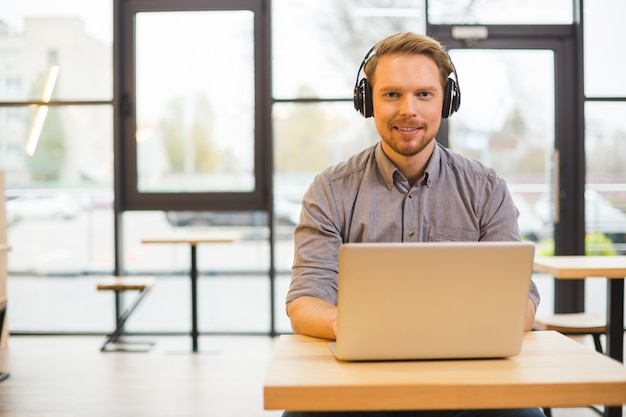 Piacevole simpatico uomo seduto davanti al laptop e ti guarda mentre usi le cuffie