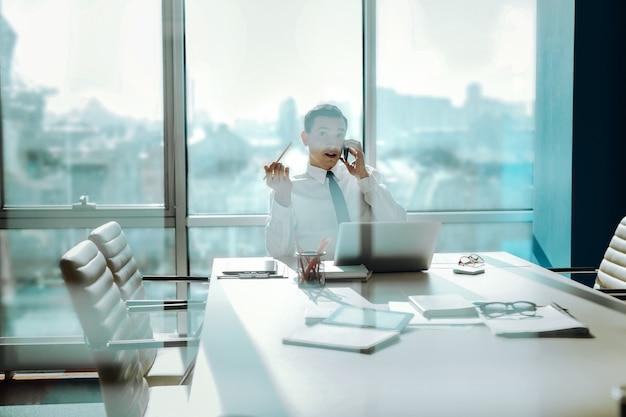 Piacevole discussione. allegro giovane impiegato che parla al telefono con il suo collega, discutendo di problemi di lavoro, mentre è seduto in una sala conferenze davanti al suo laptop
