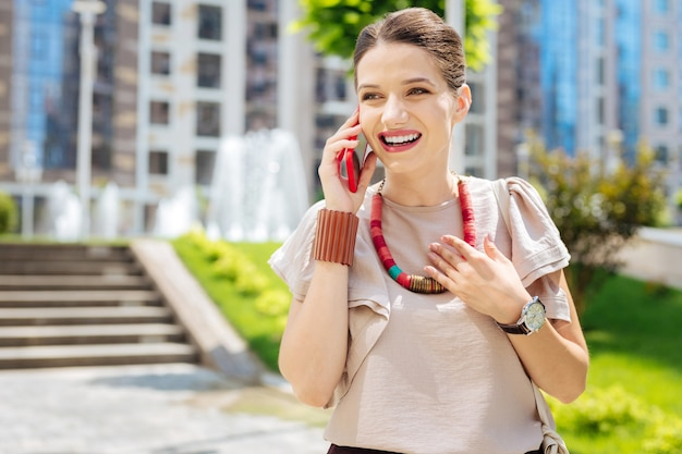 Piacevoli emozioni. felice donna positiva di essere di ottimo umore mentre parla al telefono