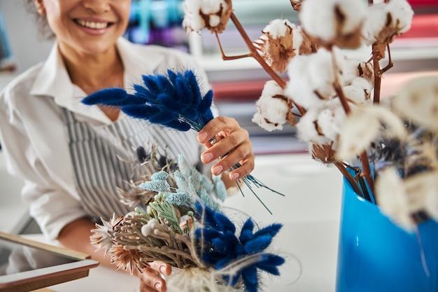 Piacevole fiorista femminile in posa con alcuni fiori blu secchi