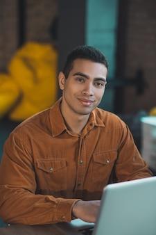 Piacevole bell'uomo che ti sorride mentre è seduto al suo posto di lavoro