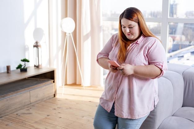 Bella donna di bell'aspetto che usa il suo smartphone mentre chatta sui social network